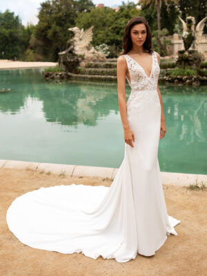 Brand new Pronovias gown, Emily. Stunning deep v front and back neckline with beaded lace detail throughout on the bodice. Lined lace on the bodice going down the back and the sides. Plain ivory fit and flare silhouette crepe skirt.
